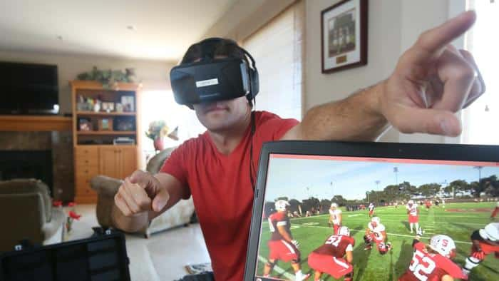 Derek Belch simulates how he can direct players on the field during a demonstration of a VR training simulator