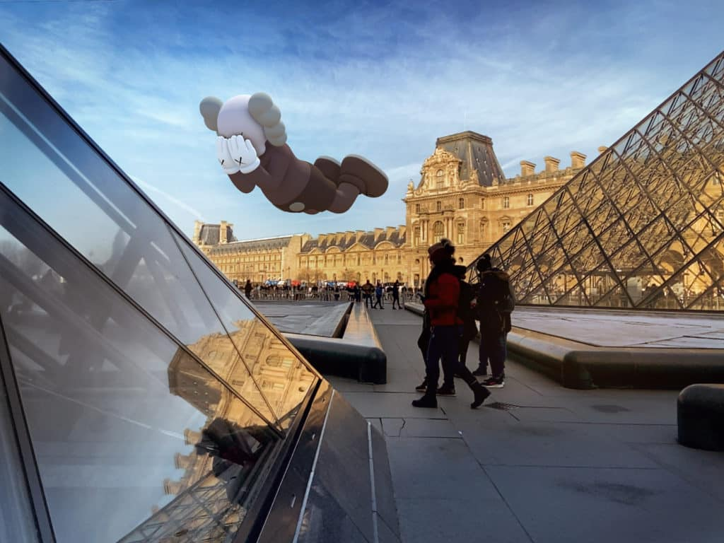 KAWS AR Art Sculptures hovering over the Louvre Pyramids in Paris.